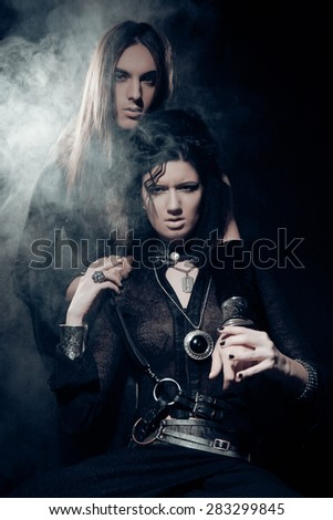 Romantic portrait of young gothic couple - man and woman over dark background. - stock photo