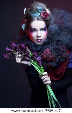 Romantic portrait of young woman in creative image and with dark flowers in her hands