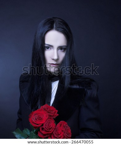 Romantic portrait of young woman in gothic man image posing with red roses - stock photo