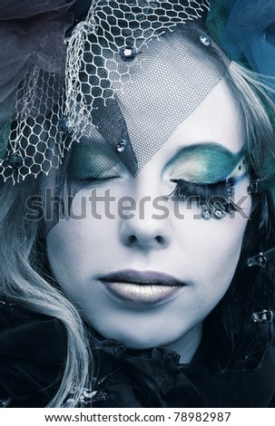 Romantic portrait of young woman with bright creative make-up in fantactic hat - stock photo
