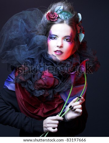Romantic portrait oj young woman in creative image and with dark flowers in her hands