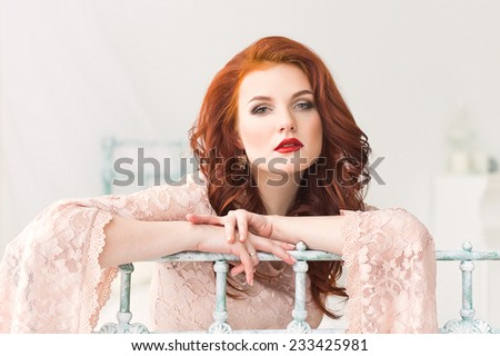Romantic red-haired woman in gentle dress in bright room - stock photo
