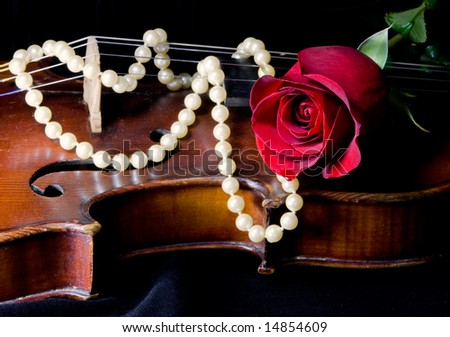Romantic red rose and pearls on a violin - stock photo