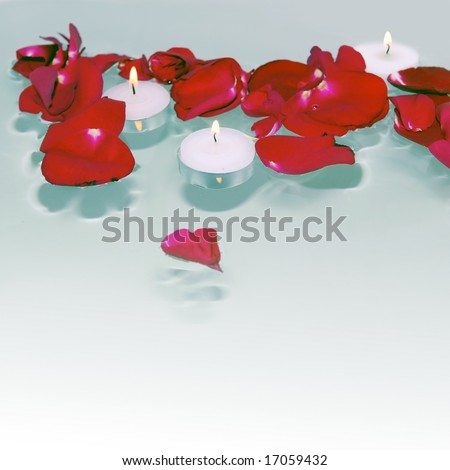 Romantic red rose petals and burning white candles floating on water with square background and heart shaped petal on foreground - stock photo