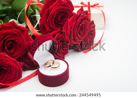 Romantic red roses with wedding rings. Valentine day background. - stock photo