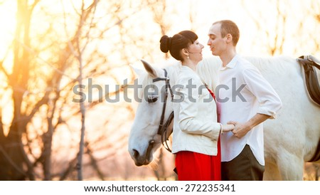 Romantic retro dating. Grazing horse on the background. - stock photo