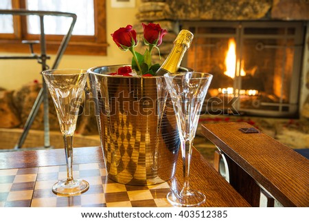 romantic room with champagne bucket and roses - stock photo