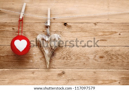 Romantic rustic Valentines greeting background with handcrafted wooden heart and colourful textile heart bauble hanging on a line from pegs over natural wooden boards - stock photo