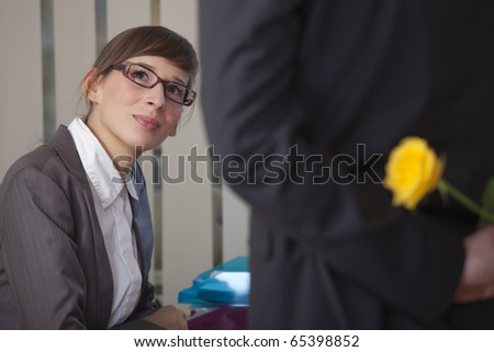 romantic scene in office - man hiding flower behind his back - stock photo
