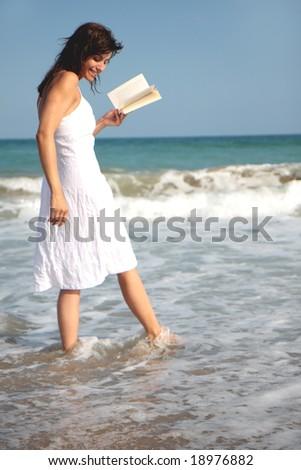 Romantic scene of a book holding woman walking the coastline - stock photo