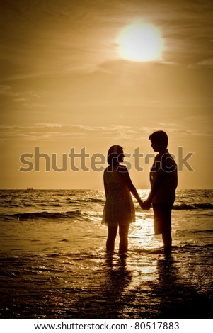 romantic Scene of couples on the Beach with sunset - stock photo