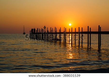 Romantic scene of the wooden jetty on the sea backlit by the declining sun with red sunset sky as a background.  - stock photo