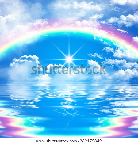 romantic seascape scene with rainbow on cloudy blue sky and bright sunshine, reflection in water, with waves - stock photo