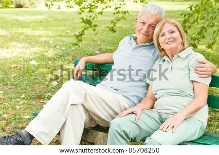 Romantic senior couple relaxed on the park bench. - stock photo