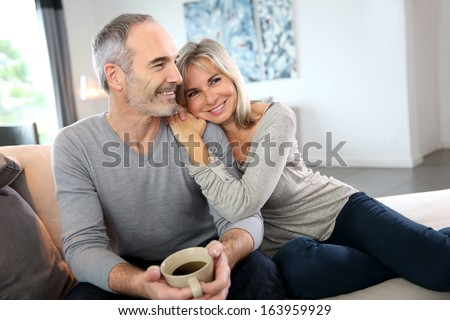 Romantic senior couple relaxing in couch  - stock photo