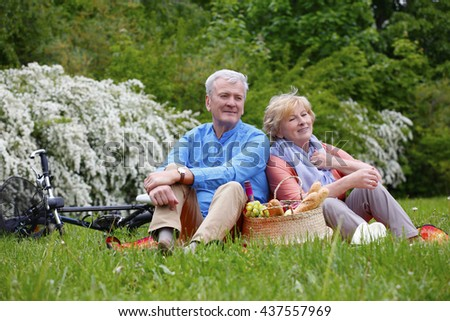 Romantic senior couple seated on the grass and relaxing while picnic. - stock photo