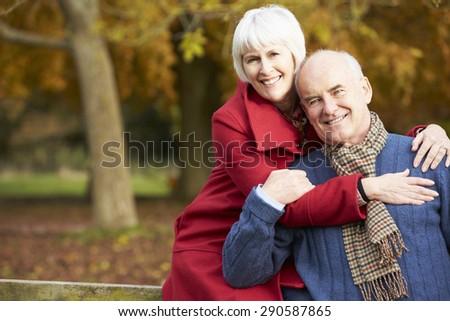 Romantic Senior Couple Sitting On Fence In Autumn Woodland - stock photo