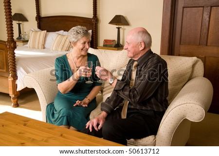 Romantic senior older couple celebrating in beautiful hotel suite - stock photo