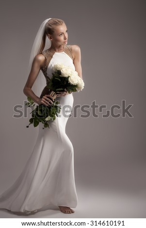 Romantic sensual blonde woman in wedding fashionable dress holding bouquet of white roses. Studio shot. Attractive bride.