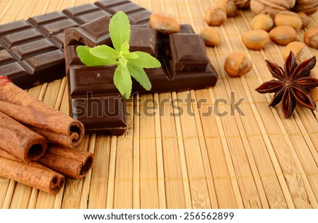 Romantic set of chocolate,anise,nuts,cinnamon with leaves of sage on wooden mat - stock photo