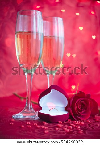 Romantic setup with two glasses of champagne, rose and engagement ring on red background with bokeh in form of hearts. Marriage Proposal with diamond ring. Valentine's day background.