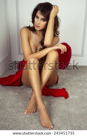 Romantic sexy brunette woman sitting on carpet. Girl with long slim legs. Valentine's day. - stock photo