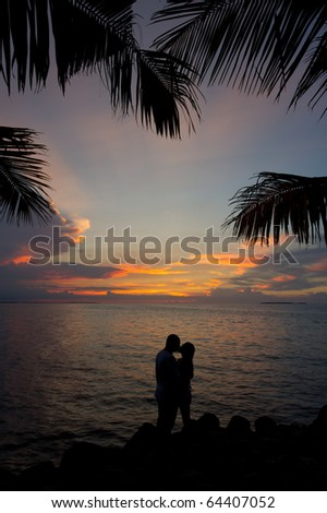 romantic silhouette couple kissing in the sunset - stock photo