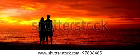 Romantic silhouette of a loving couple on honeymoon looking at a beautiful red sky sunset in Maldives, Indian Ocean. - stock photo