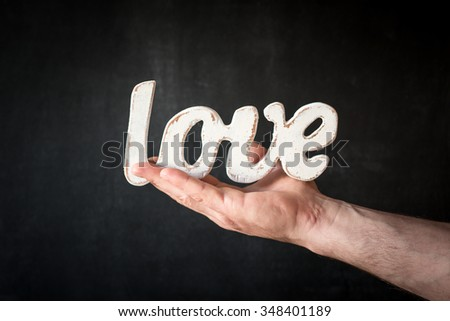 Romantic still life,men hold in hand a wooden love. Valentine's day concept.Soft focus