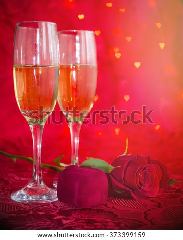 Romantic still life with champagne, gift box and red rose on red background with bokeh in heart form. Marriage Proposal. Romantic Dinner: table place setting for Valentine's Day with diamond ring. - stock photo