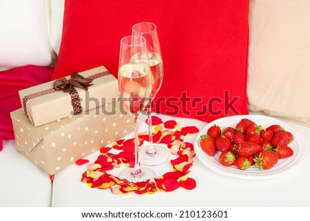 Romantic still life with champagne, strawberry and petals of roses on sofa - stock photo