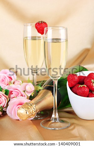 Romantic still life with champagne, strawberry and pink roses, on color fabric background