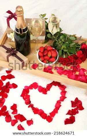 Romantic still life with champagne, strawberry and roses on bed - stock photo
