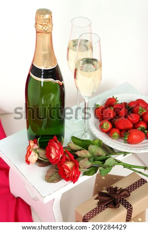 Romantic still life with champagne, strawberry and roses on sofa - stock photo