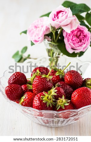 Romantic still life with  strawberries and pink roses.  Bunch of ripe strawberry in a glass bowl on white table - stock photo