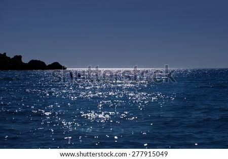 Romantic sunset and couple in the sea, beautiful sunset and man and woman swimming in the sea, couple swimming in blue romantic sunset, blue dream, summer holidays in Malta,Tufieha bay - stock photo