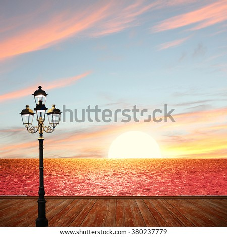 romantic sunset ocean scenery with wooden boardwalk and lantern - stock photo