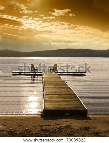 Romantic sunset setting of beach, water and chairs - stock photo