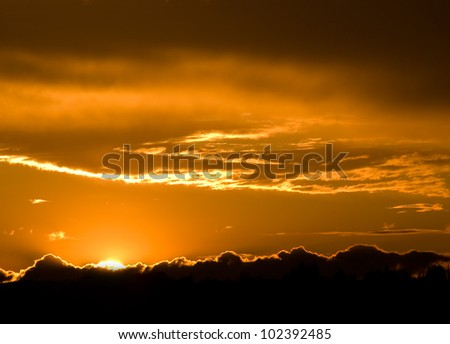 Romantic sunset with clouds and orange sky