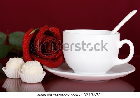 Romantic surprise in the form of a red rose, tea and chocolates
