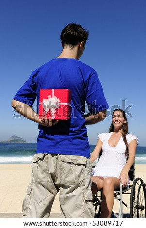 romantic surprise: man with a gift for his handicapped girlfriend - stock photo