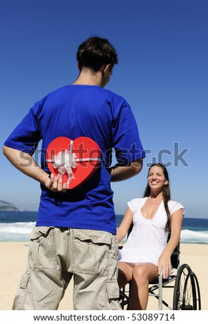 romantic surprise: man with a gift for his handicapped wife - stock photo