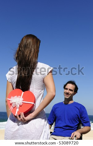 romantic surprise: woman with a gift for his handicapped husband - stock photo