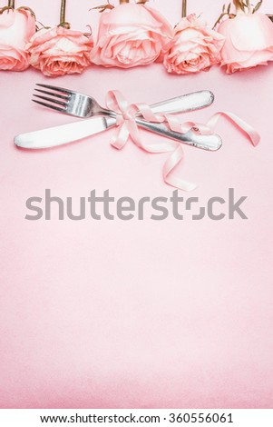 Romantic table place setting with ribbon and roses border decoration on pink pale background, top view, vertical - stock photo