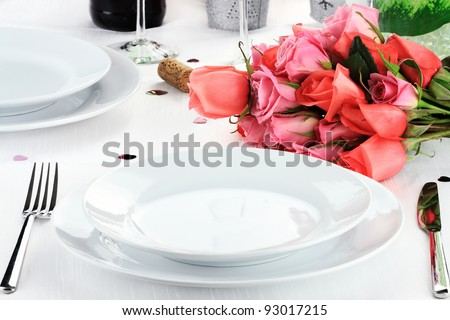 Romantic table setting for two with a bouquet of roses. Shallow depth of field. - stock photo