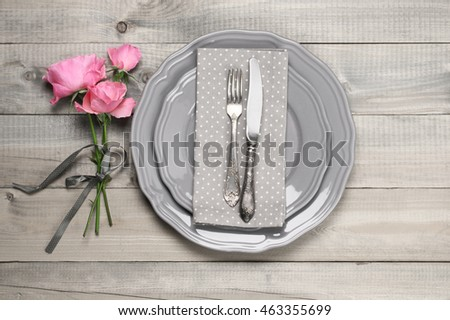 Romantic table setting: grey plates, vintage fork and knife, napkin and pink roses on rustic wooden table. Top view point.
