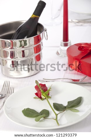 Romantic table setting with rose  and cutlery - stock photo
