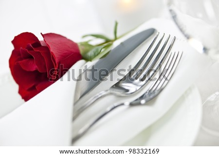 Romantic table setting with rose plates and cutlery - stock photo
