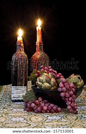 Romantic table with candles dripping with melted wax and grapes - old world still life - stock photo