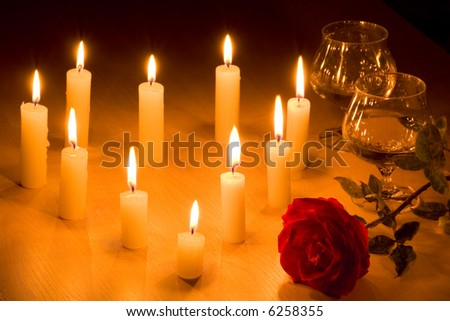 Romantic table with flaming  heart of candles, two glasses of wine and red rose. - stock photo